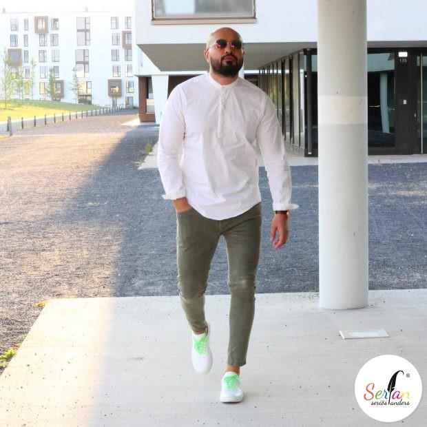 Hasan in senen weißen Serfan Sneakern mit grünen Details.